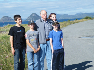 """Our patriarch with his grandchildren at Argentia, with """"Mae West"""" in the background."""