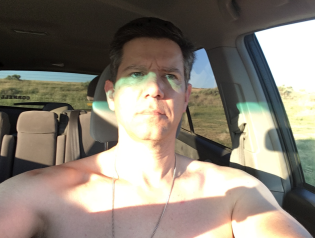 Cooling off with the truck's AC, after dispatching a horsefly. Also, I ripped my shirt David Banner-style while pounding tent stakes.